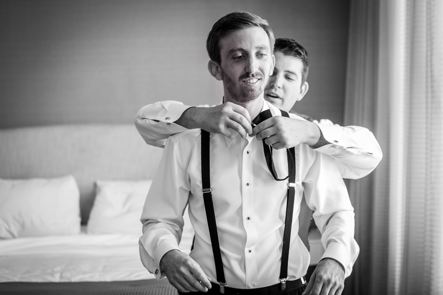Black and white photo of the groom getting his bow tie on, Hotel del Coronado wedding, Cavin Elizabeth Photography