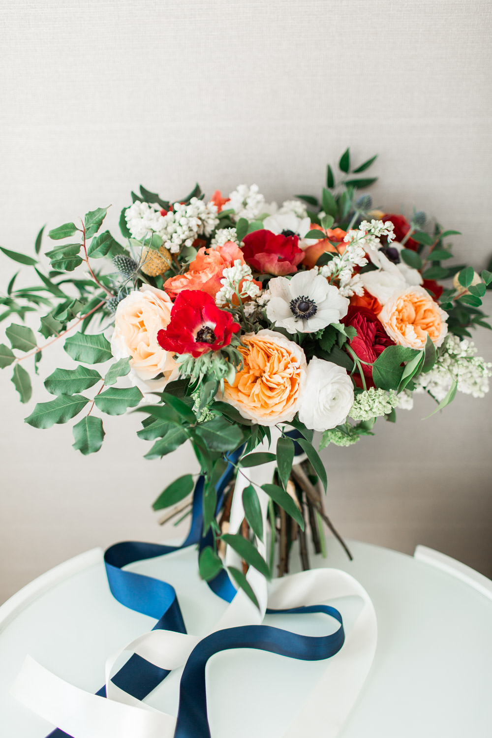 Red green peach and white bridal bouquet with white and navy ribbons, Cavin Elizabeth Photography