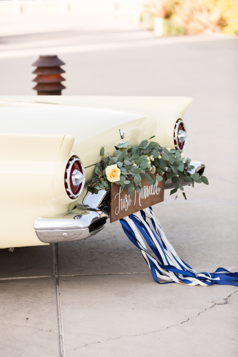 Floral just married sign on the back of a Yellow vintage wedding getaway car, Cavin Elizabeth Photography