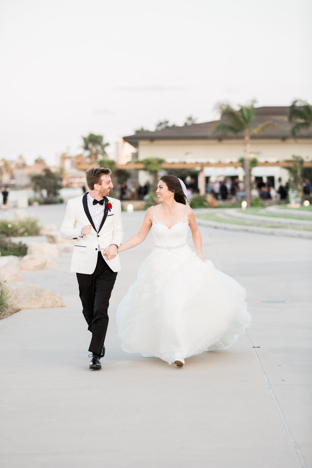 Bride and groom running together in a portrait at the Coronado Community Center, Cavin Elizabeth Photography