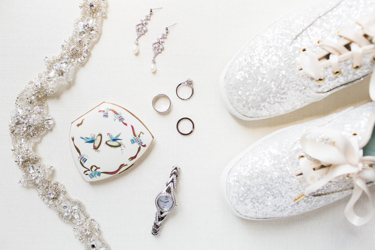 Wedding styling flatlay of watch and vintage mirror case and sash and earrings and rings and Kate Spade Keds in white glitter, Cavin Elizabeth Photography