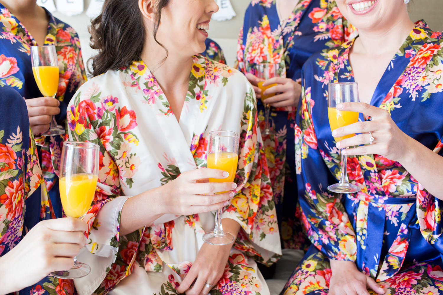Bride and bridesmaids in blue and white robes with mimosas, Cavin Elizabeth Photography