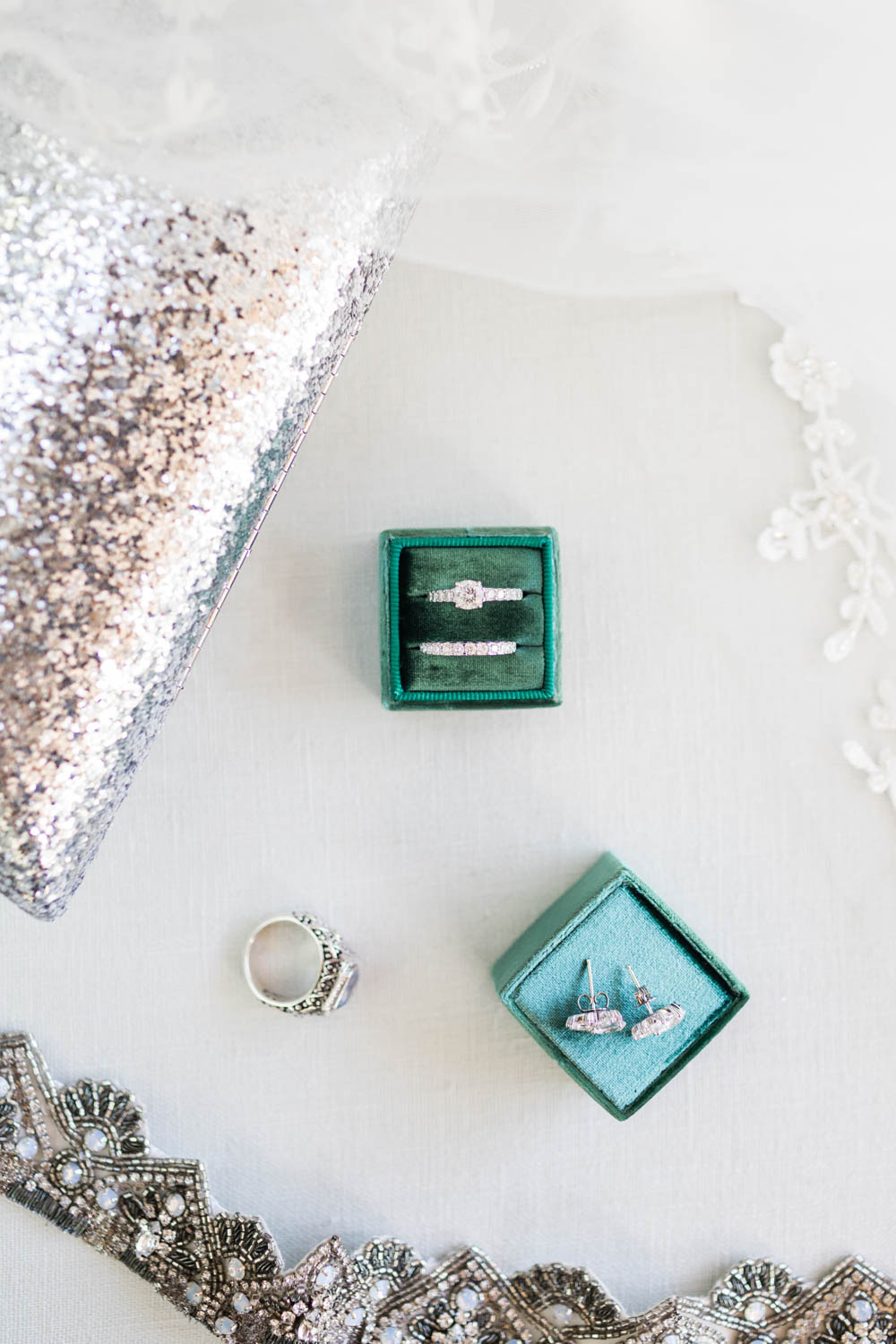 Wedding rings in a green Mrs Box styled with bridal details and jewelry, Vibrant Winter Wedding at Omni Rancho Las Palmas, Cavin Elizabeth Photography