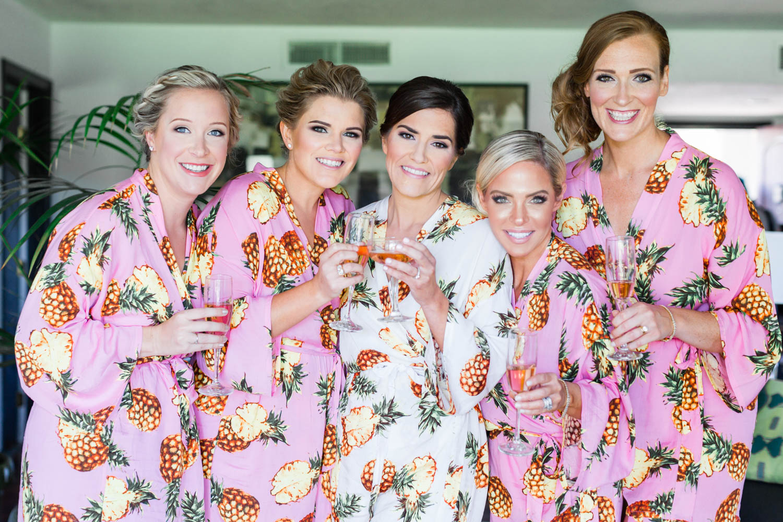 Bridesmaids in pink tropical pineapple robes, Vibrant Winter Wedding at Omni Rancho Las Palmas, Cavin Elizabeth Photography