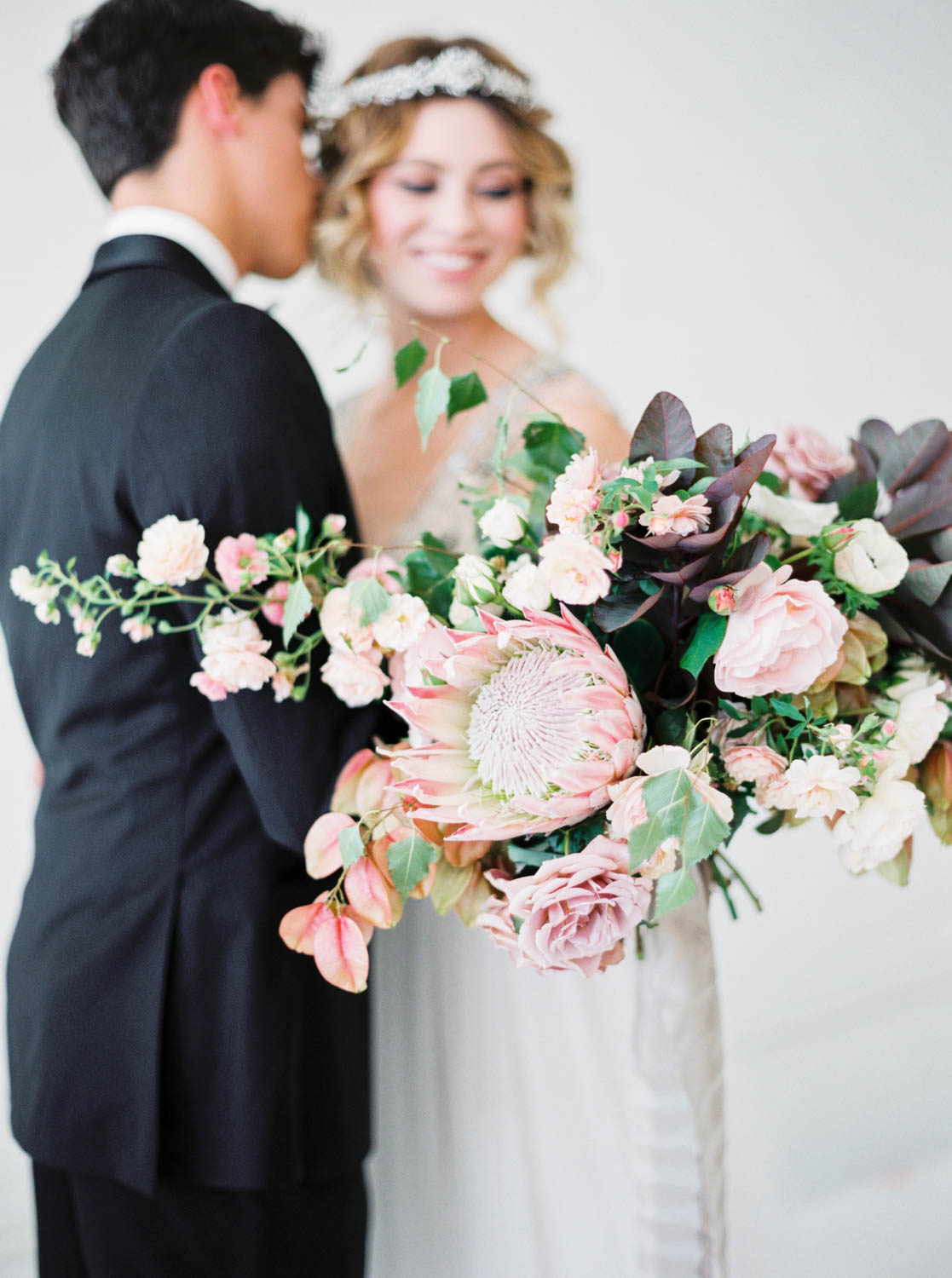 Bride holding bouquet of pink green deep colors with pops of white by Oak and the Owl, Cavin Elizabeth Photography