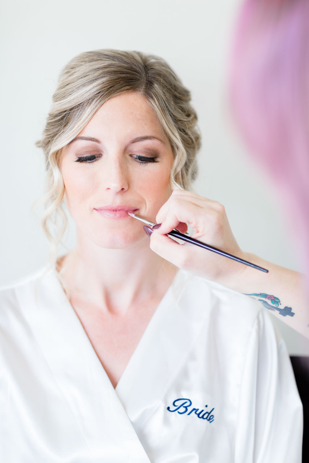 Bride getting lips touched up wearing a white bridal robe, Cavin Elizabeth Photography