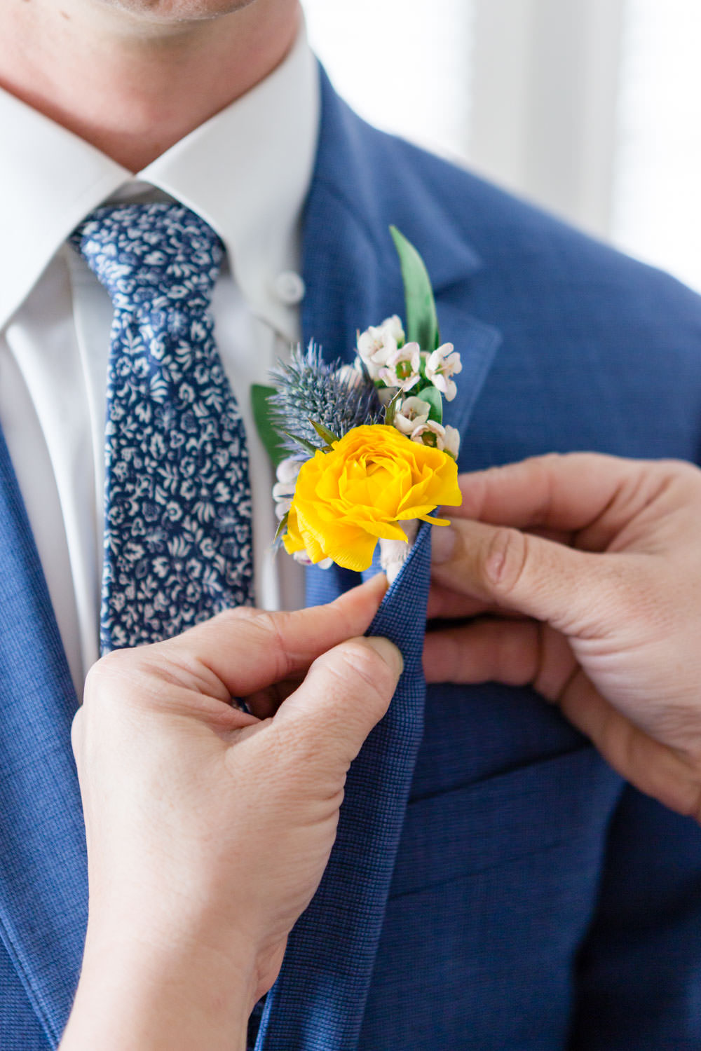 Yellow boutonniere being pinned to a blue suit, La Quinta Resort Wedding in Palm Springs, Cavin Elizabeth Photography