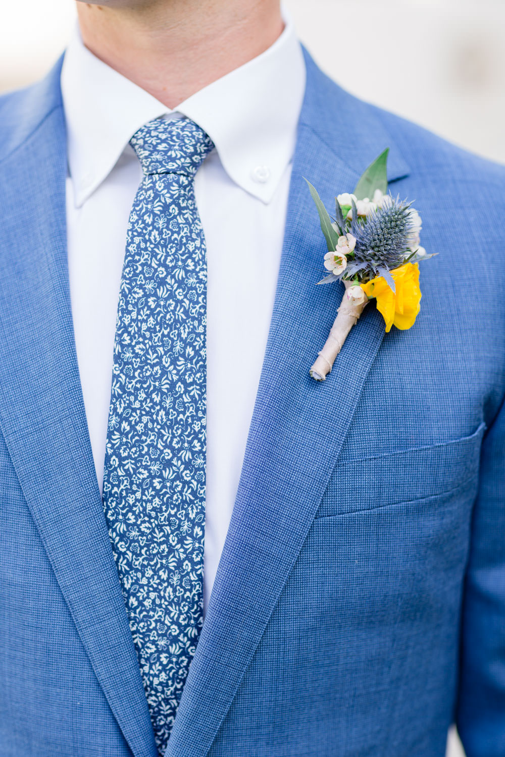 Yellow and blue boutonniere on a blue suit with a blue and white tie, Cavin Elizabeth Photography