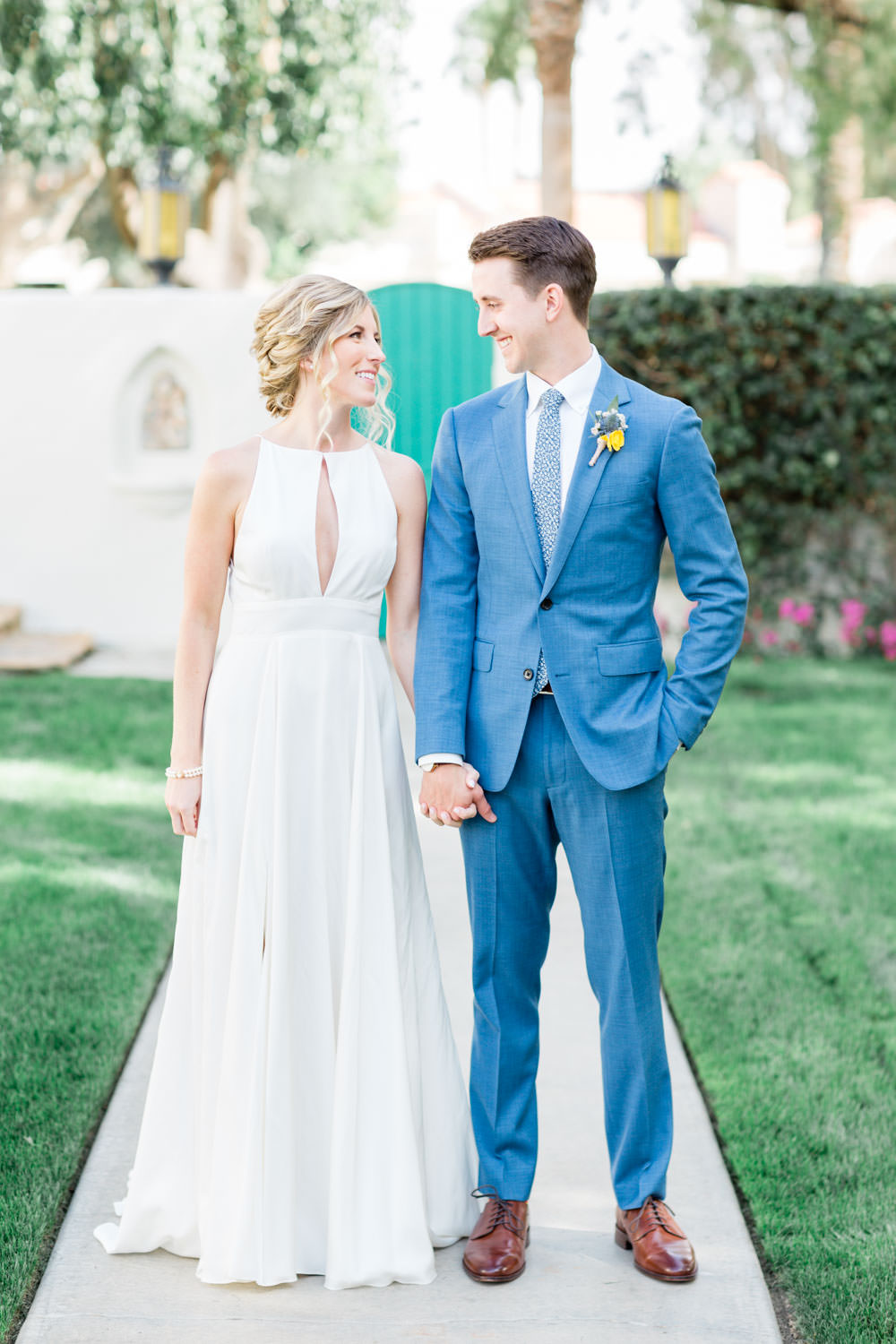 Bride and groom portraits, groom in blue suit with yellow boutonniere, bride wearing Rebecca Schoneveld Lincoln gown with pink yellow green and orange bridal bouquetfirst look, La Quinta Resort Wedding in Palm Springs, Cavin Elizabeth Photography