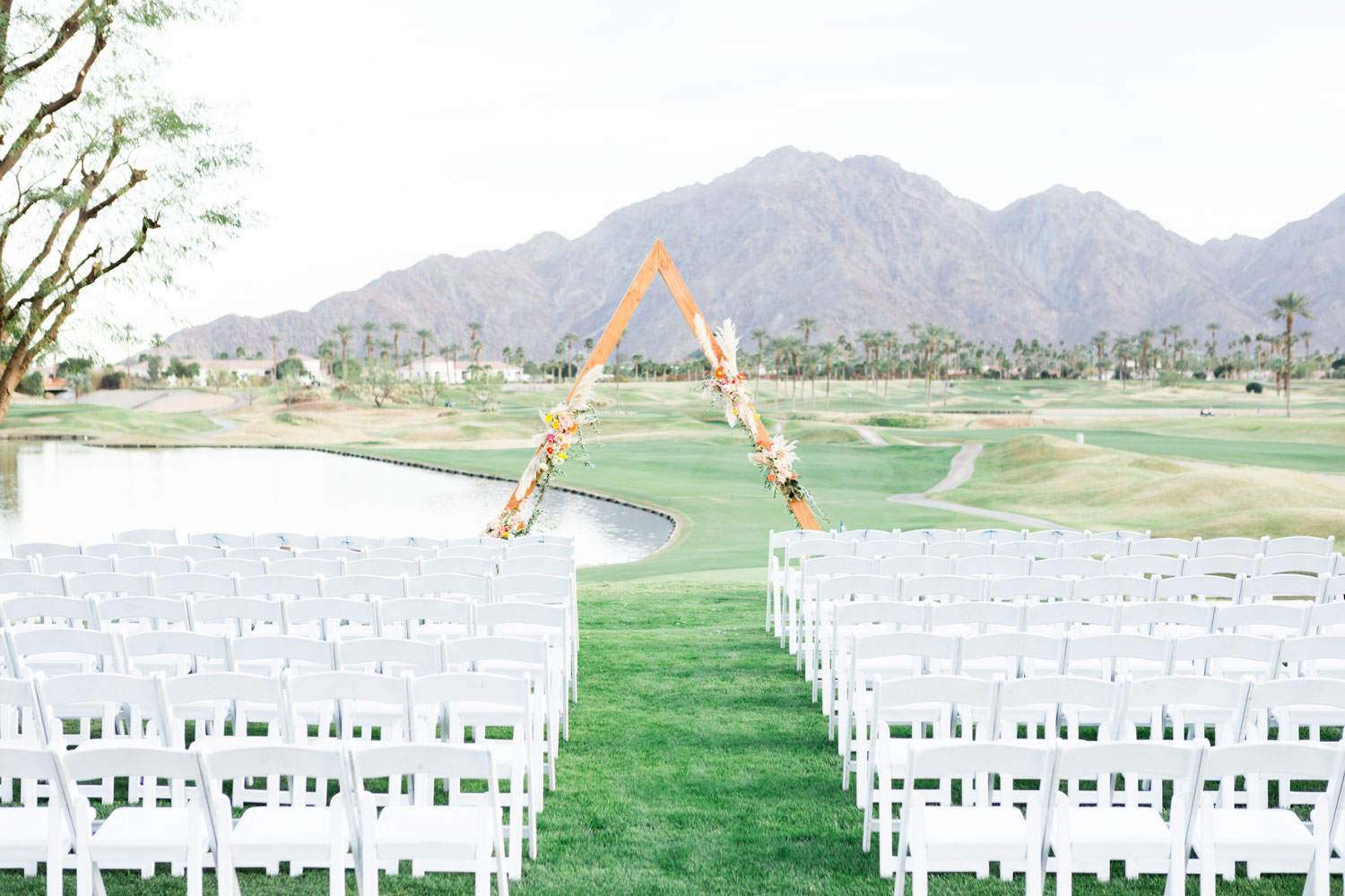 La Quinta Resort wedding ceremony with triangular arch with pampas grass and pink orange yellow flowers with views of the golf course and mountains, Cavin Elizabeth Photography