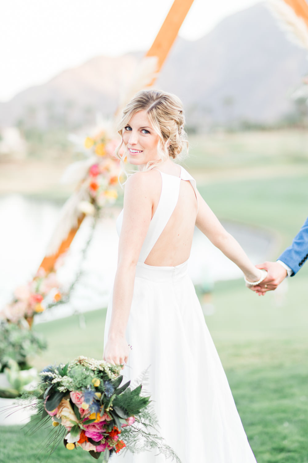 La Quinta Resort wedding bride and groom portraits in front of triangular arch with pampas grass and pink orange yellow flowers with views of the golf course and mountains, Cavin Elizabeth Photography