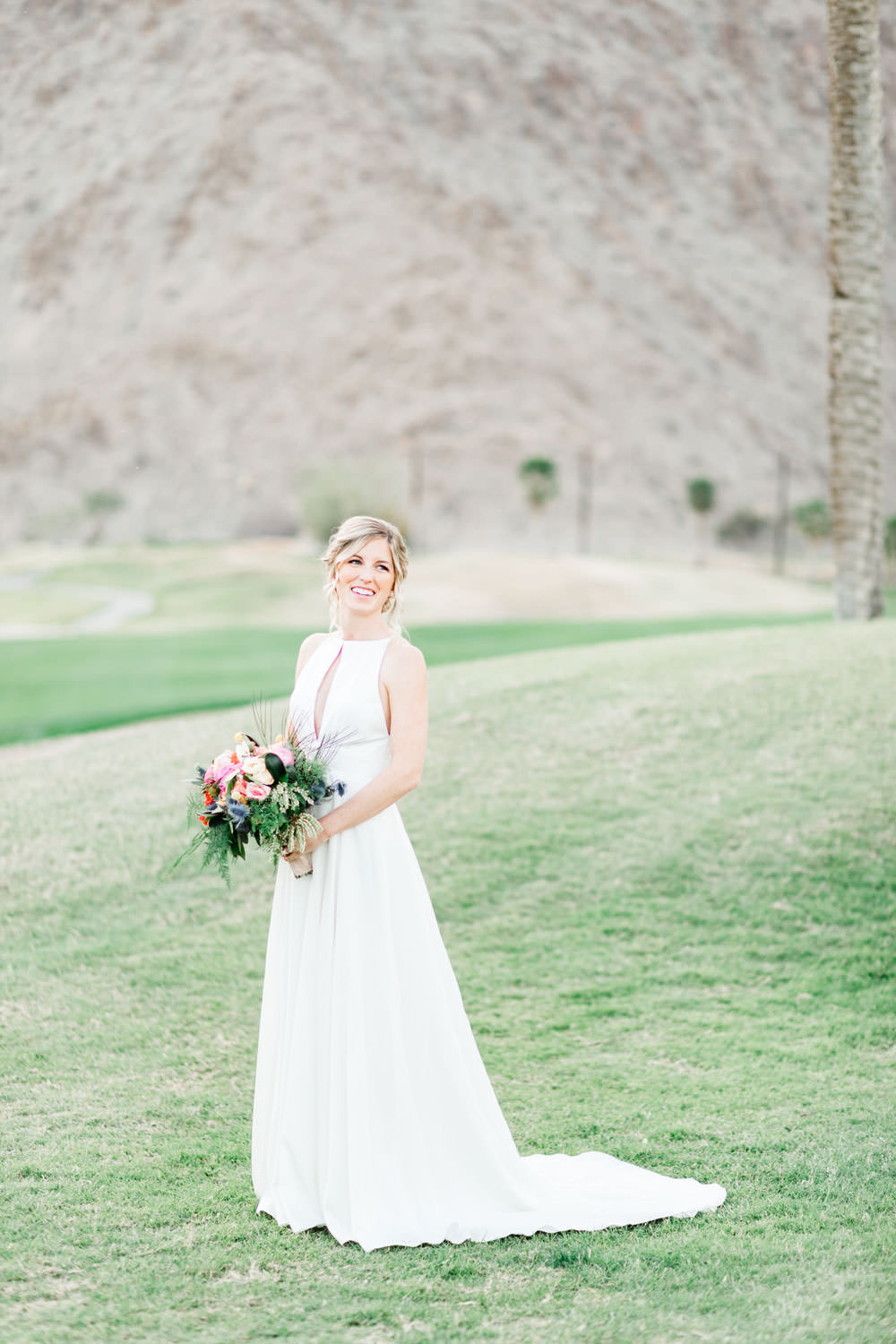 Bridal portrait of a bride in a Lincoln gown by Rebecca Schoneveld holding a bouquet in front of Palm Springs mountains, Cavin Elizabeth Photography