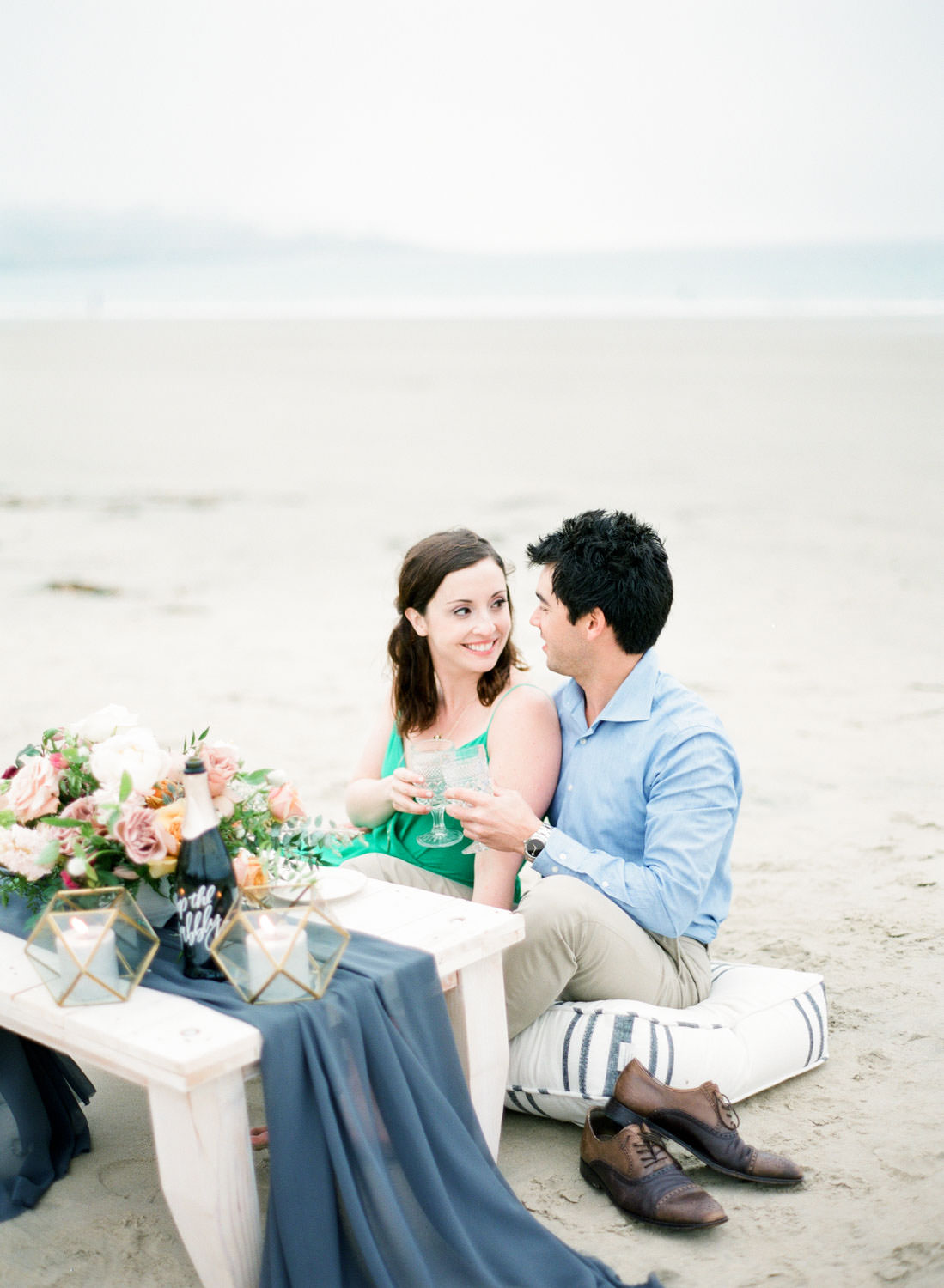 Green dress, Styled engagement shoot in San Diego, Champagne picnic captured on 400h film Contax 645 of a white table with deep blue silk runner and a flower arrangement with calligraphy champagne bottle and geometric candle containers, Cavin Elizabeth Photography