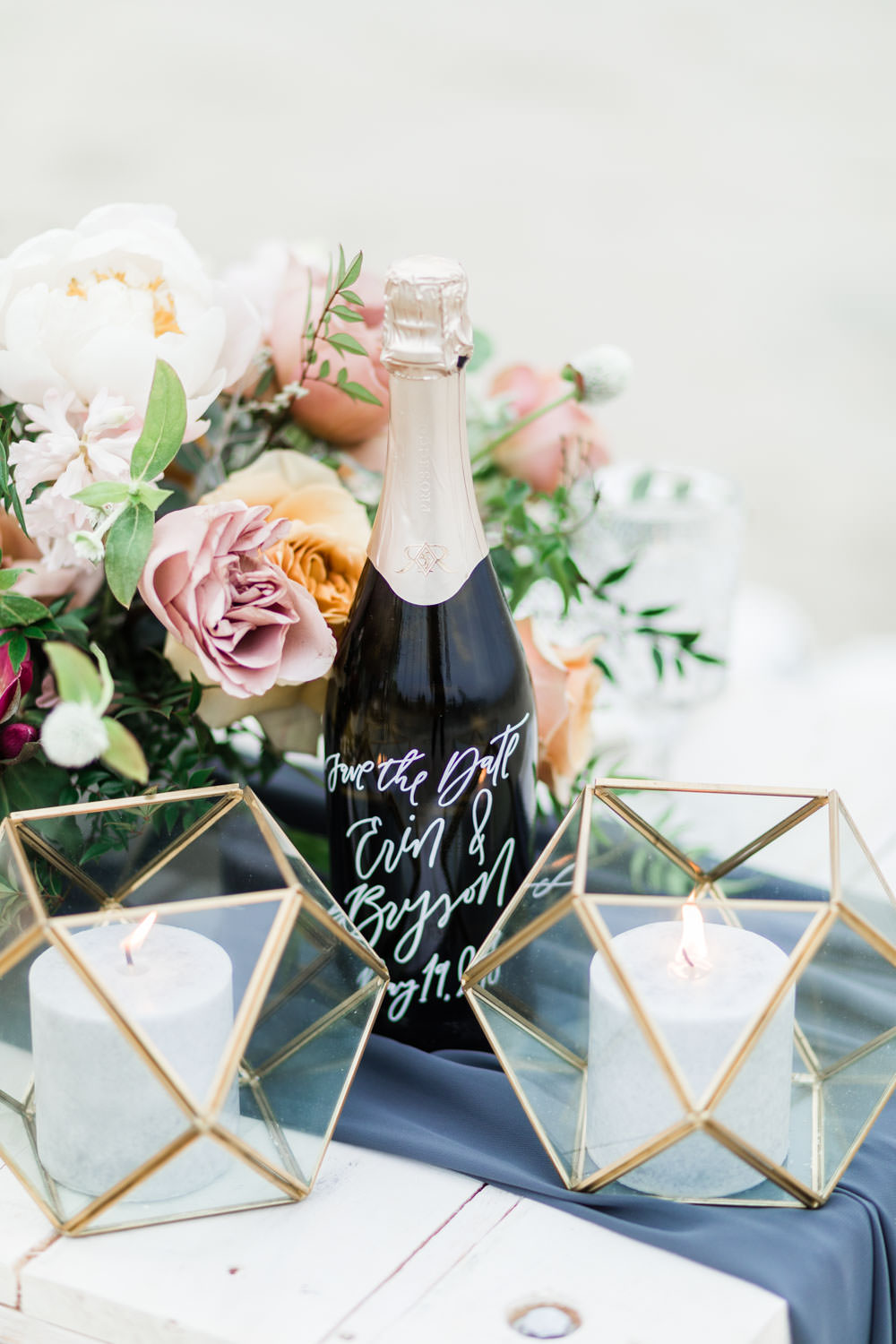 Styled engagement shoot in San Diego, Champagne picnic of a white table with deep blue silk runner and a flower arrangement with calligraphy champagne bottle and geometric candle containers, Cavin Elizabeth Photography
