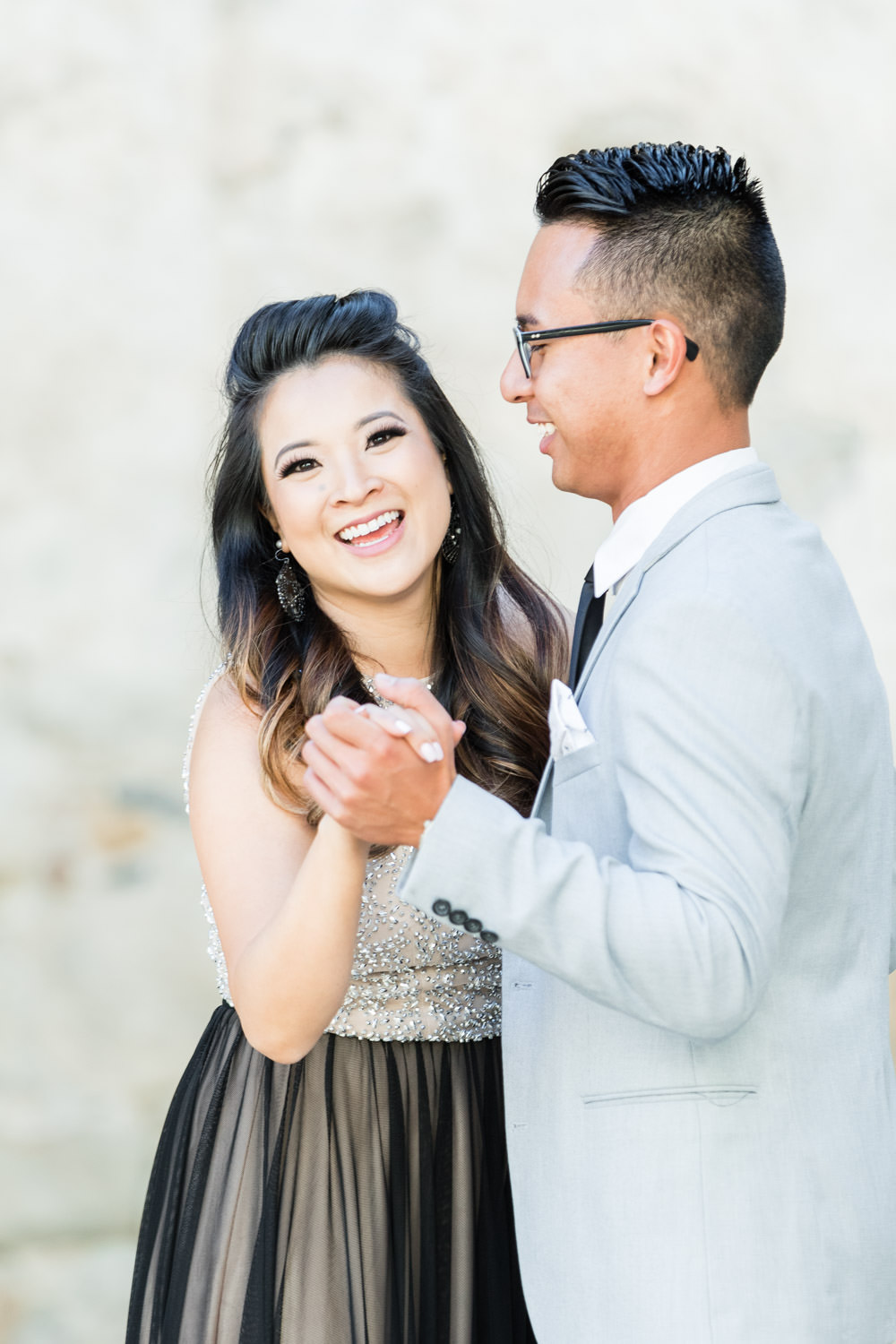 Suit and tie with black shirt and sparkly engagement outfit, Mission San Juan Capistrano Engagement Photos with ruins and weathered stone, Cavin Elizabeth Photography