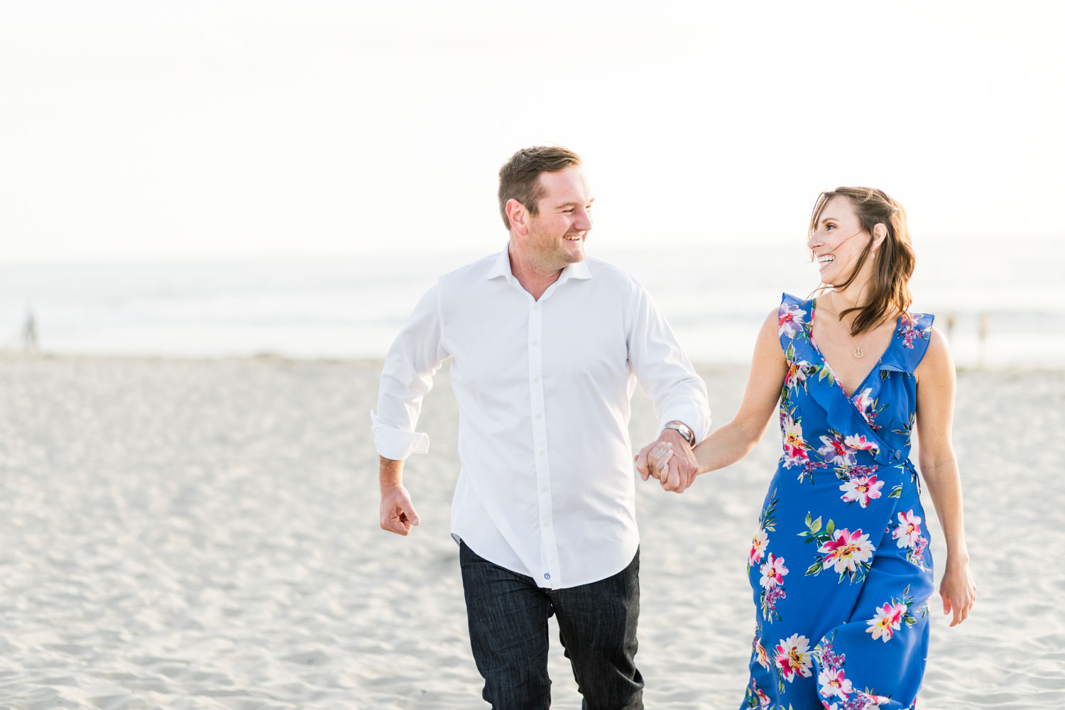 Couple running in engagement photo, Blue floral dress, Mission Beach Engagement Photo on the sand, Cavin Elizabeth Photography