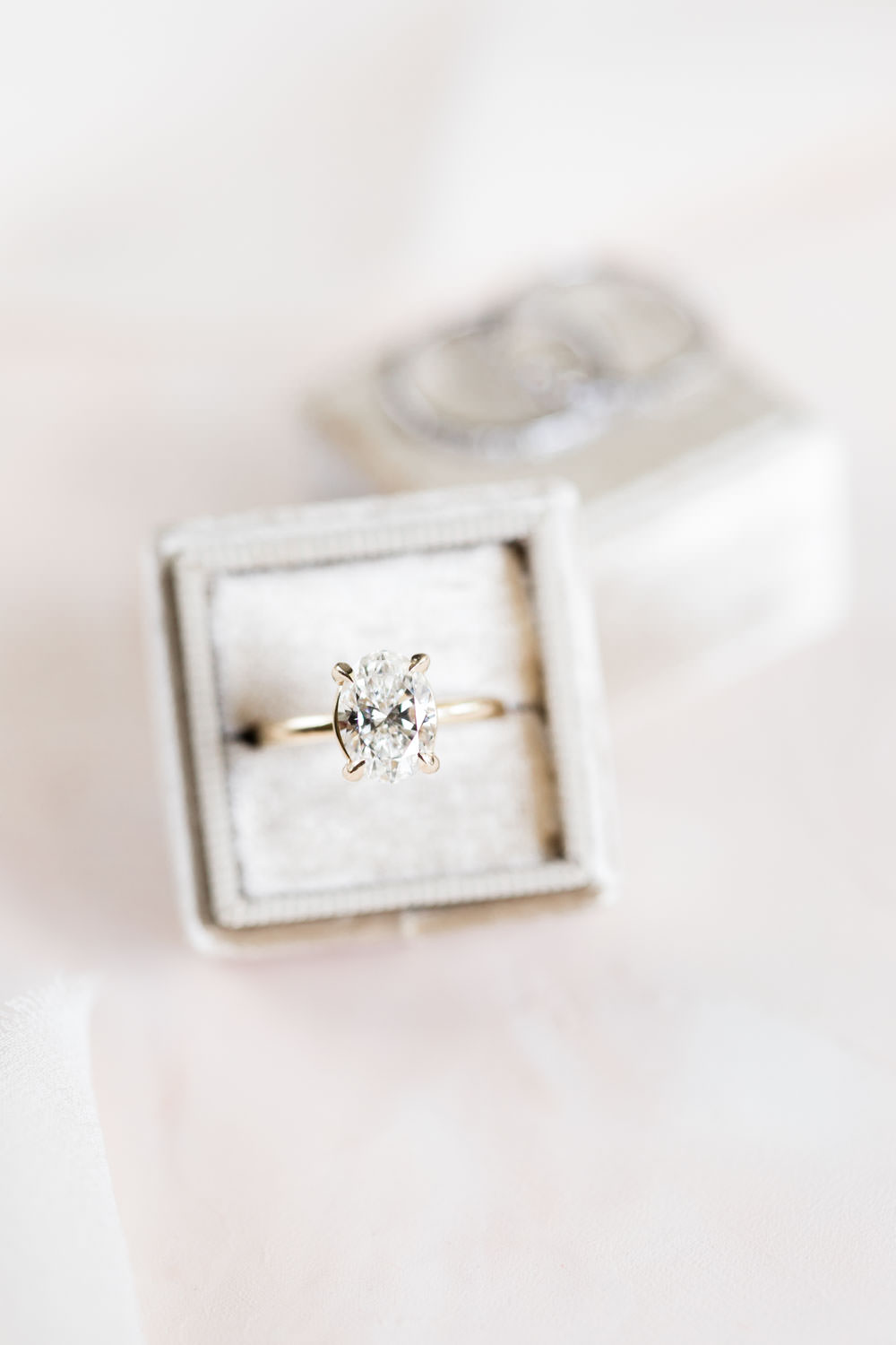 Oval diamond engagement ring in a gray Mrs Box, Cavin Elizabeth Photography