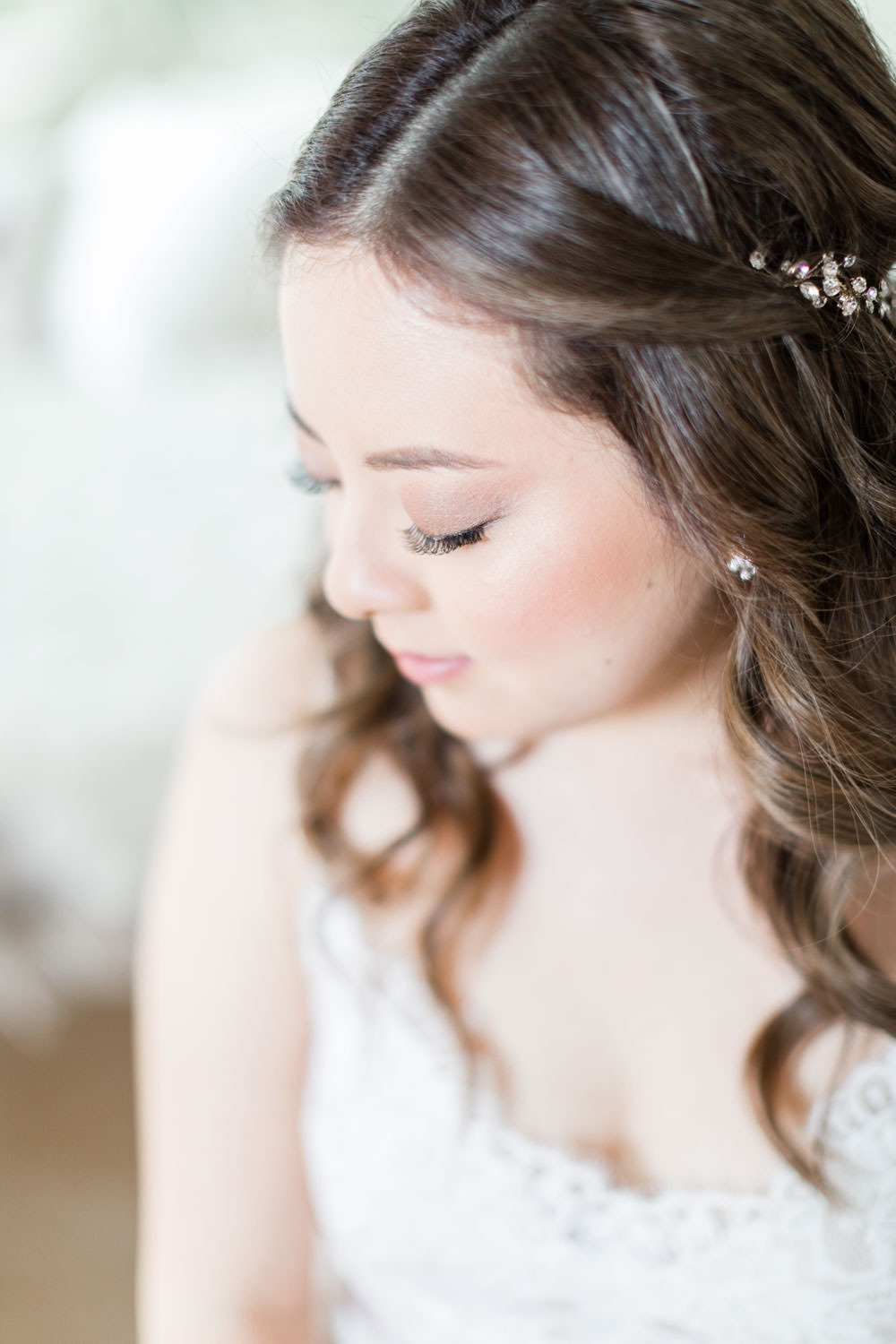 Natural bridal makeup with loose curlsBride putting on Bella Belle shoes at Ethereal Open Air Resort, Cavin Elizabeth Photography