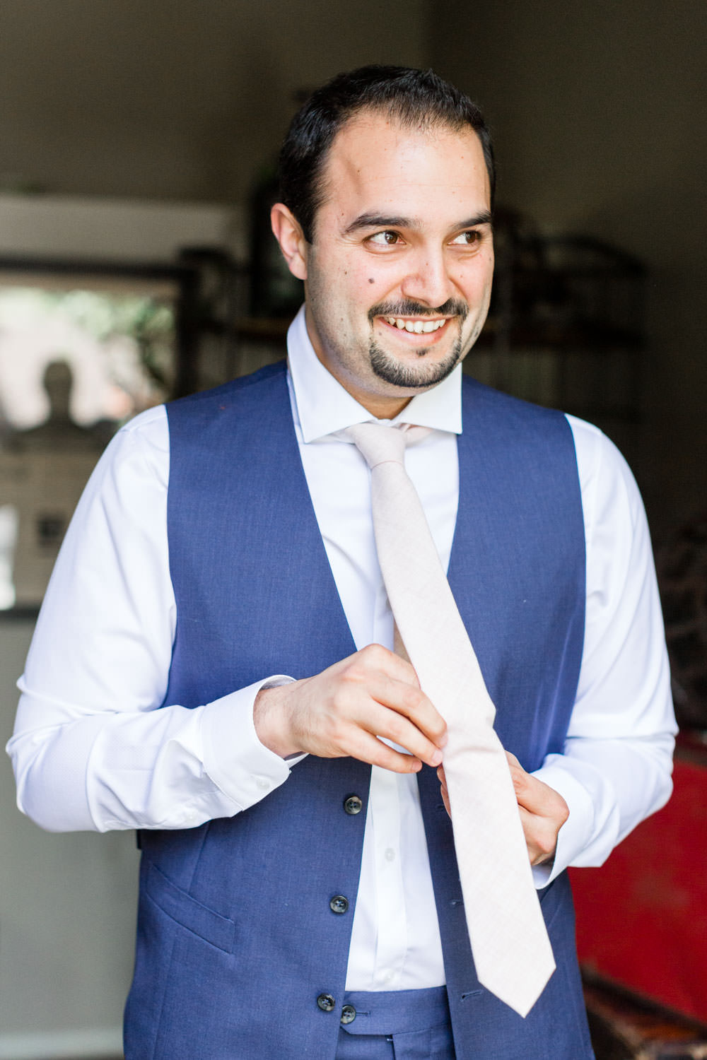 Groom smiling while putting on tie at Ethereal Open Air Resort, Cavin Elizabeth Photography