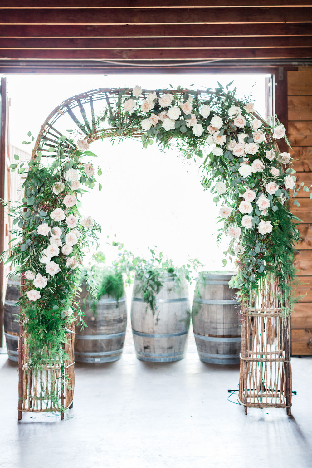 Ethereal Open Air Resort Wedding Ceremony arch with white green and blush flowers, Cavin Elizabeth Photography