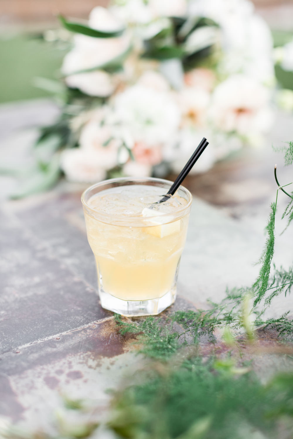 Yellow signature cocktail surrounded by flowers, Cavin Elizabeth Photography