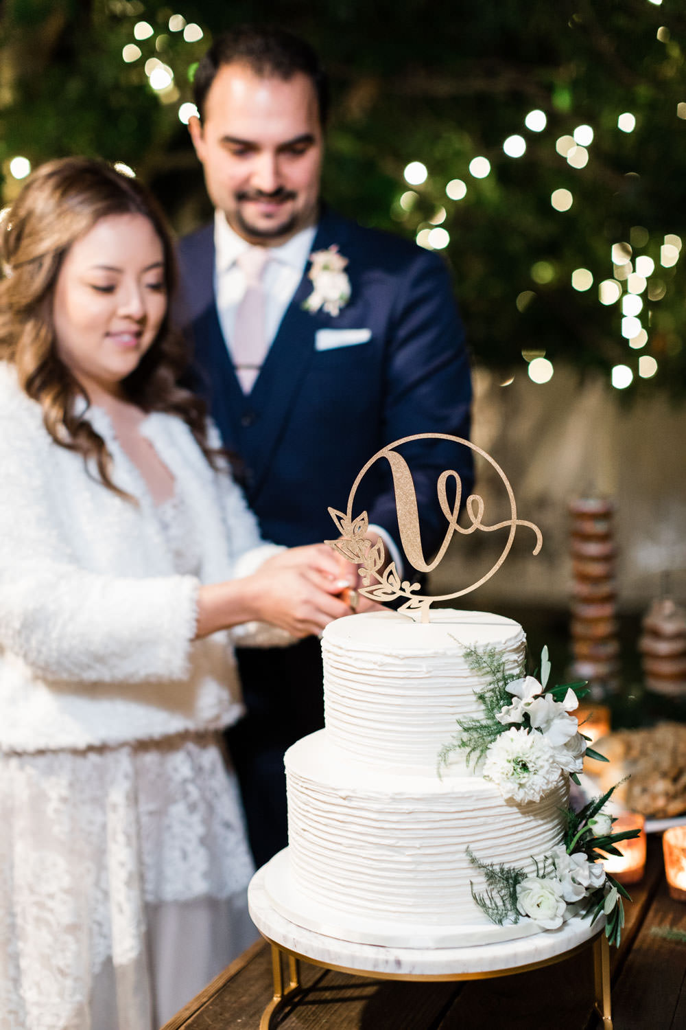 Bride and groom cut VG Donut white two tier cake, Cavin Elizabeth Photography