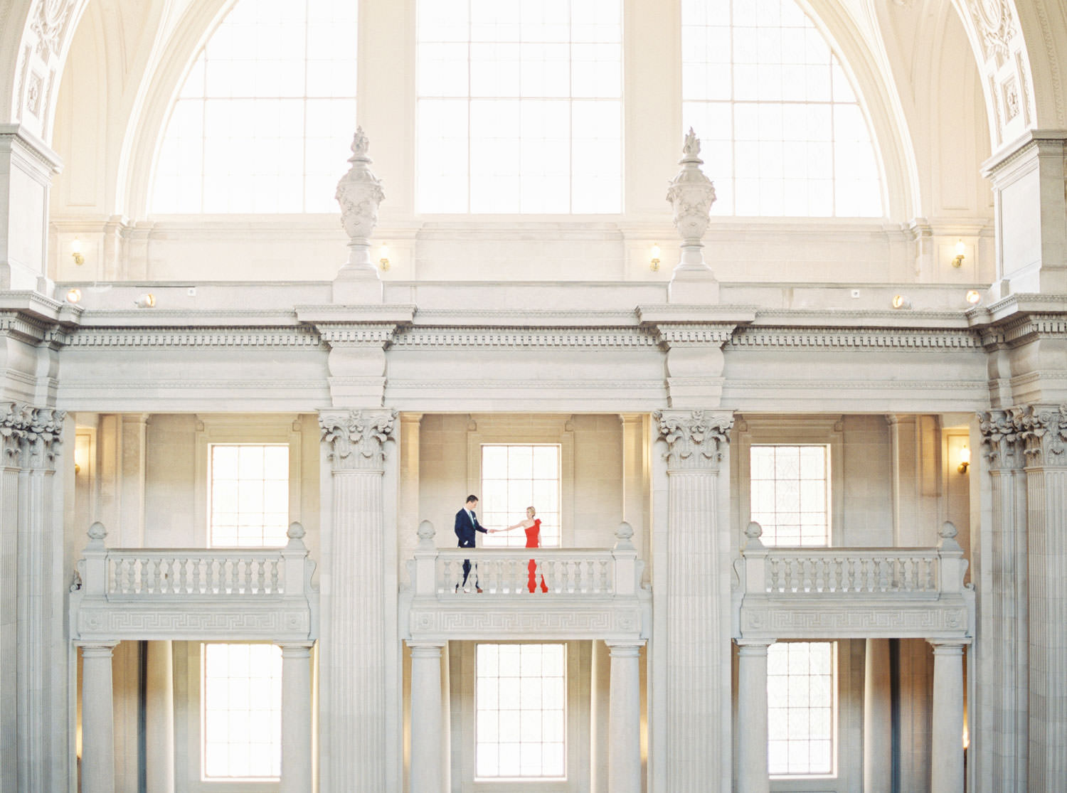 Wide architectural epic engagement photo, Bride in red dress with groom in navy suit for San Francisco City Hall Engagement Photos on the 4th floor, Cavin Elizabeth Photography