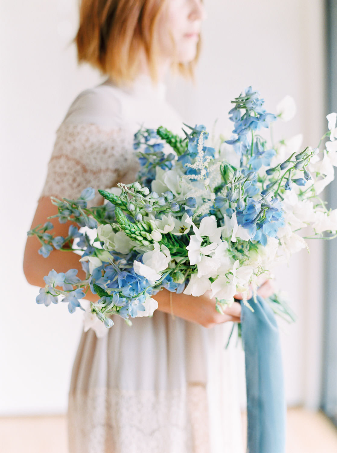 Wedding film photography image of a Bride with white and green bouquet with blue sweet peas and blue ribbons, Cavin Elizabeth Photography and Organic Flora