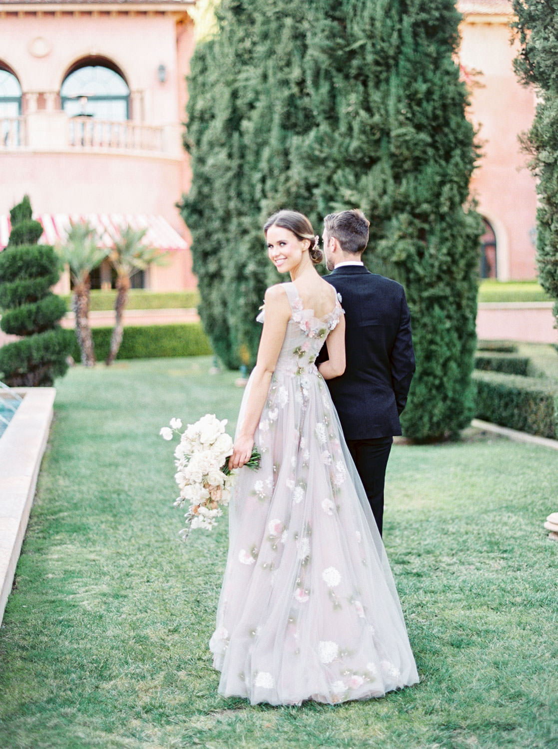 Bride walking with groom on the reflection lawn in a Marchesa blush neutral floral gown, Fairmont Grand Del Mar Wedding by Cavin Elizabeth Photography