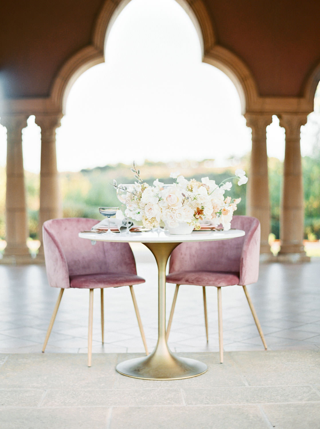 White sweetheart table with mauve pink velvet chairs with white centerpiece under Aria lawn pavilion at the Grand Del Mar, Cavin Elizabeth Photography
