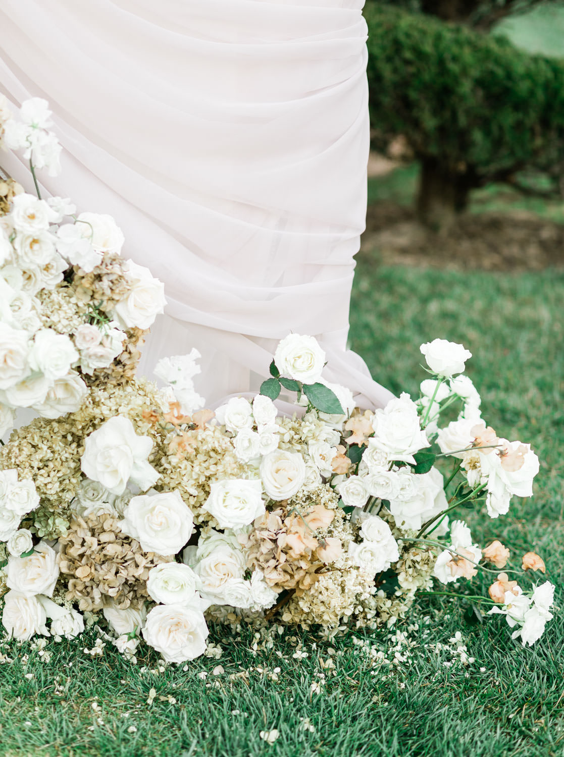Asymmetrical floral arrangement on arch, Grand del Mar wedding ceremony on reflection lawn, Cavin Elizabeth Photography