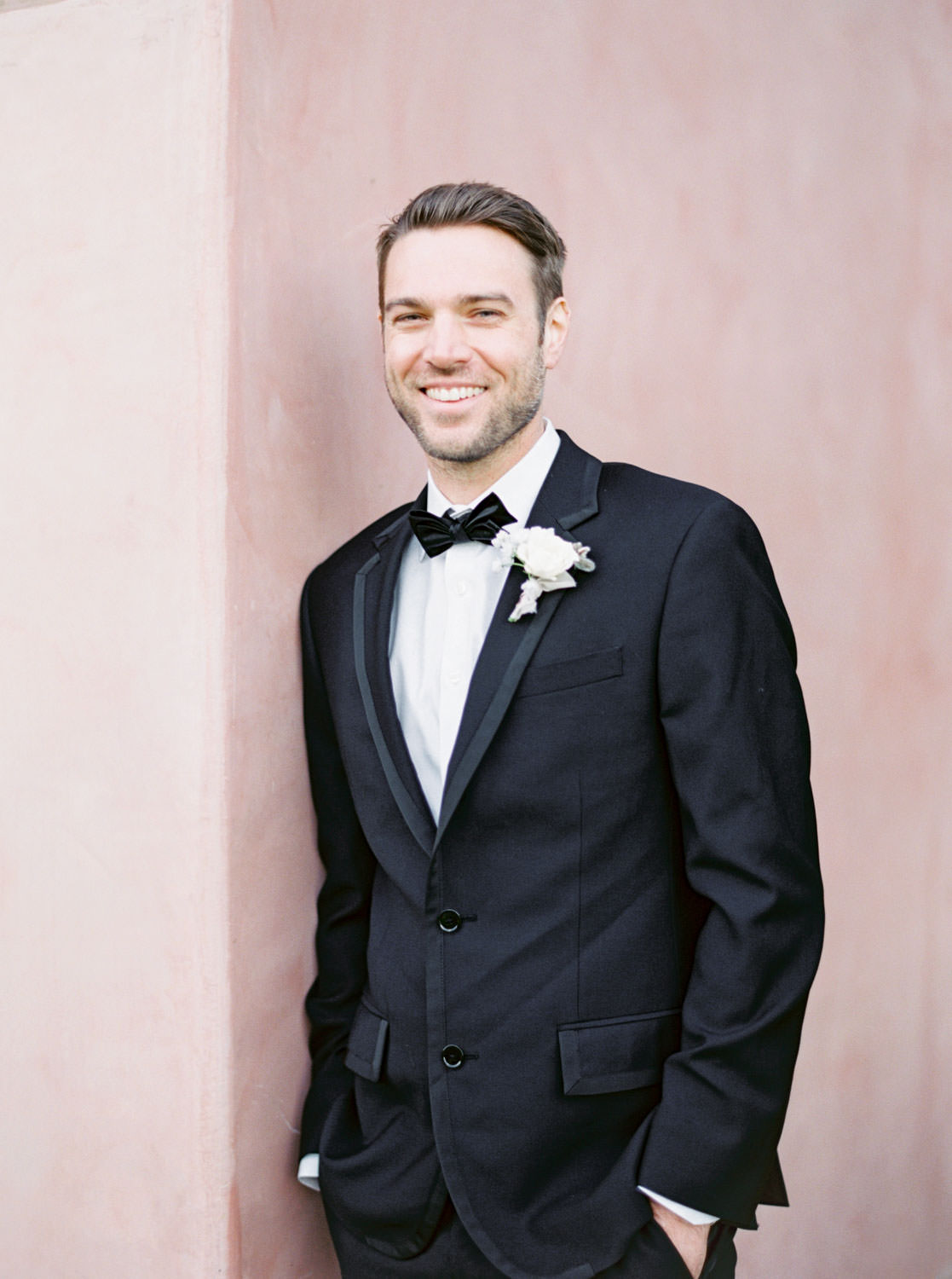Groom portrait in The Black Tux against a pink wall at Grand Del Mar, Cavin Elizabeth Photography