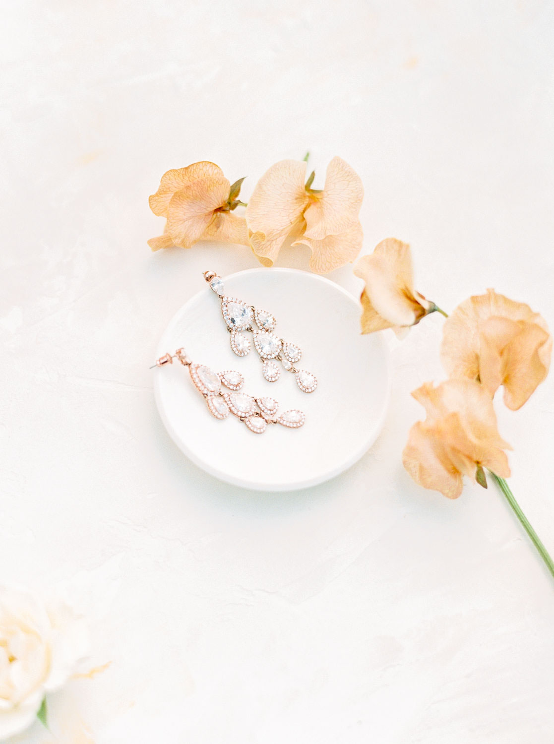 Diamond dangling earrings in a ring dish with peach sweet pea flowers, Cavin Elizabeth Photography