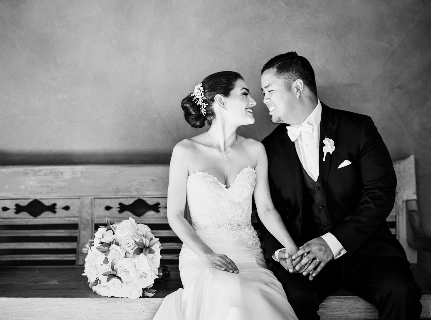 Bride and groom on a bench captured on film, Santalux Club wedding reception, Cavin Elizabeth Photography