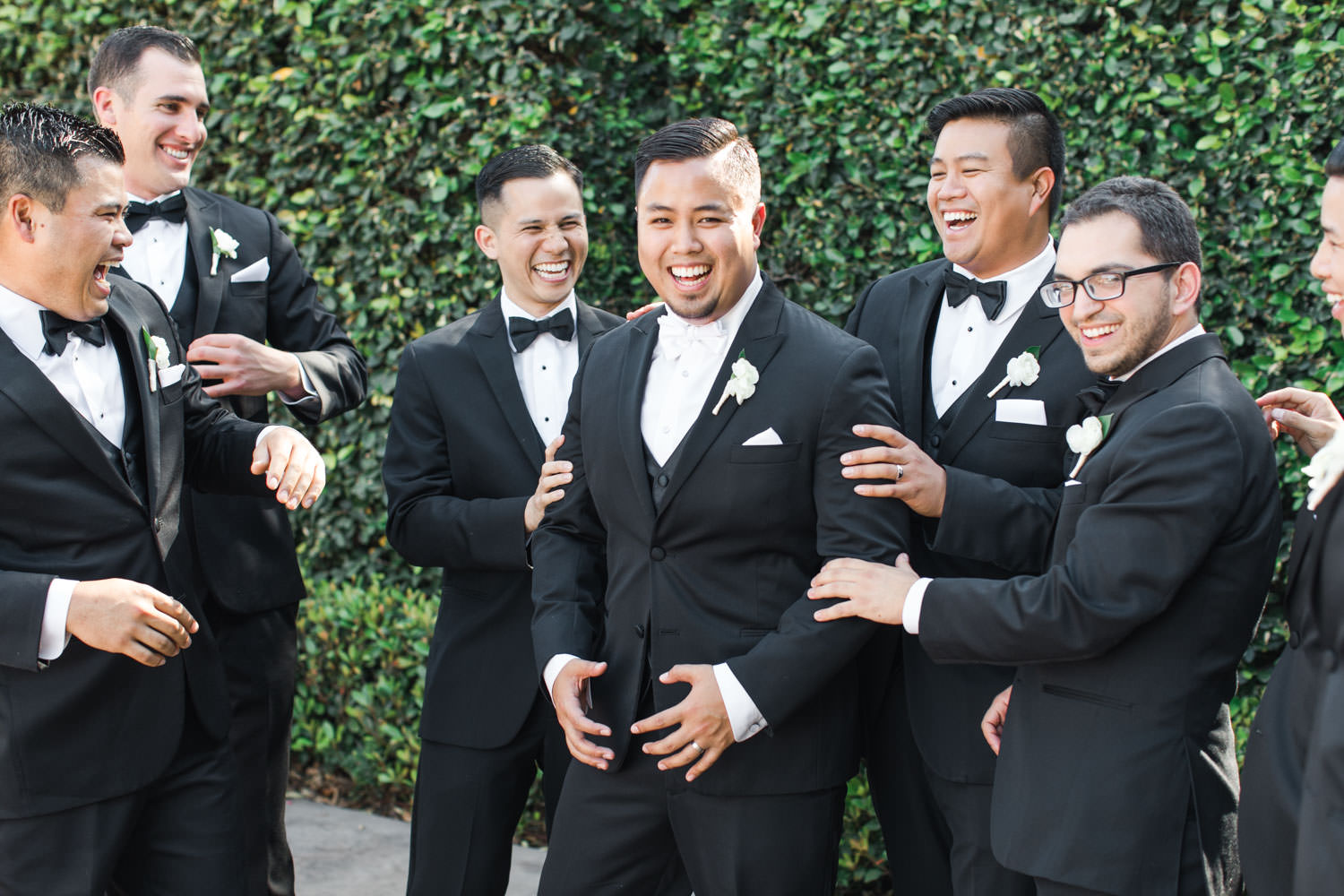 Groomsmen candid photo in front of ivy covered wall, Santalux Club wedding reception, Cavin Elizabeth Photography