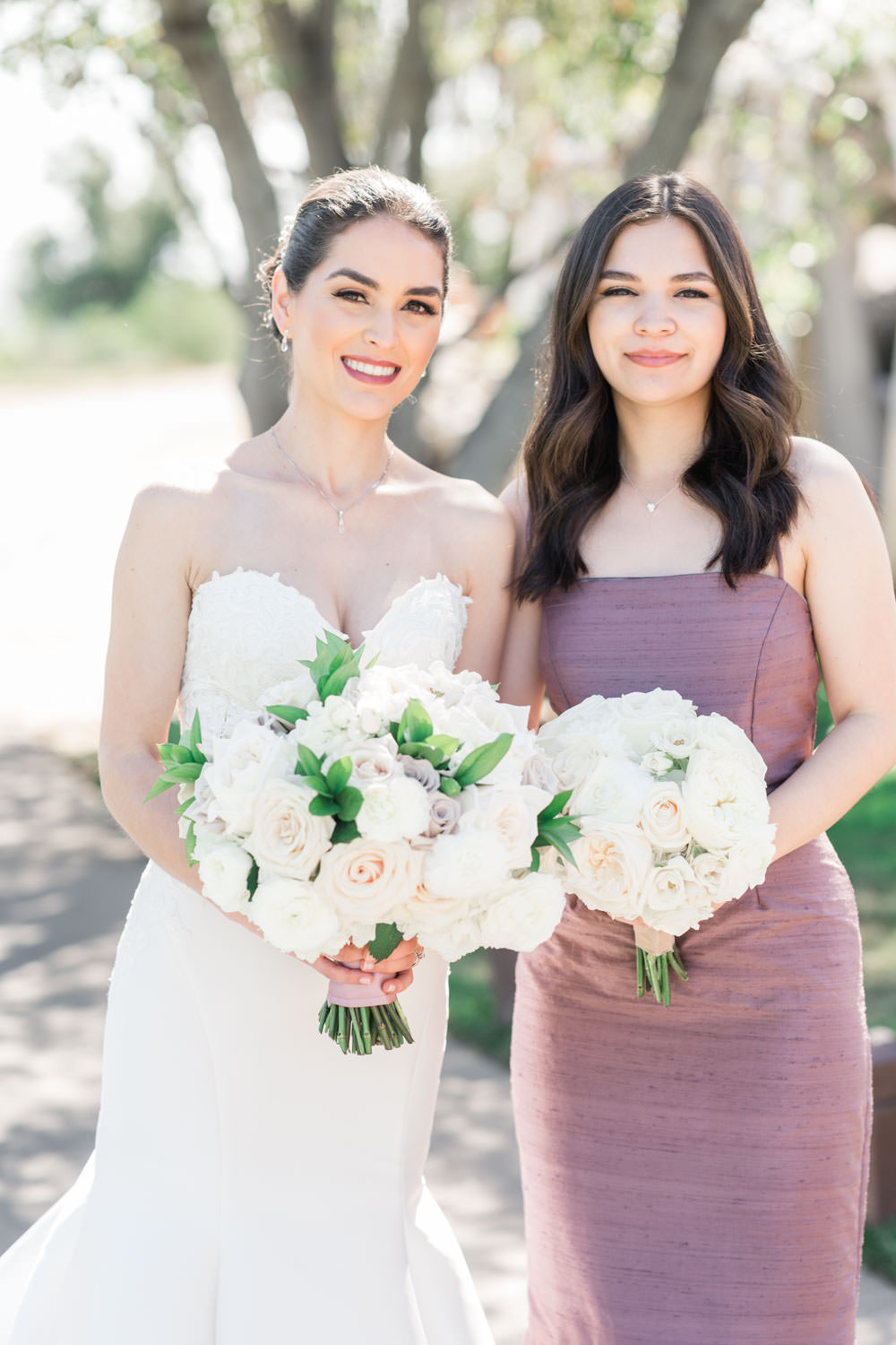 Bride with white and green bouquet with bridesmaid in mauve purple gown, Santalux Club wedding reception, Cavin Elizabeth Photography