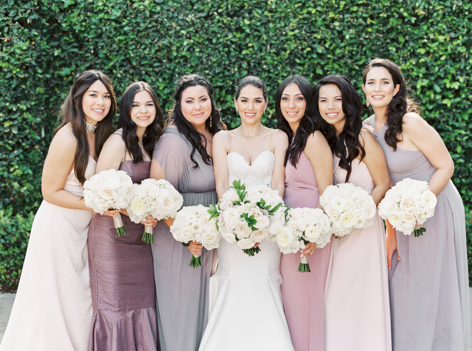 Bride with bridesmaids in blush mauve and lavender gowns in front of an ivy covered wall, Santalux Club wedding reception, Cavin Elizabeth Photography