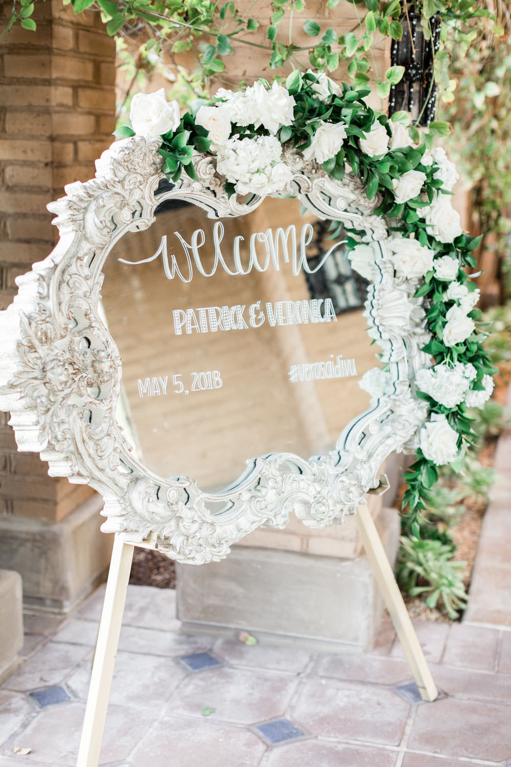 Wedding welcome sign with calligraphy on mirror with white and green flowers, Cavin Elizabeth Photography