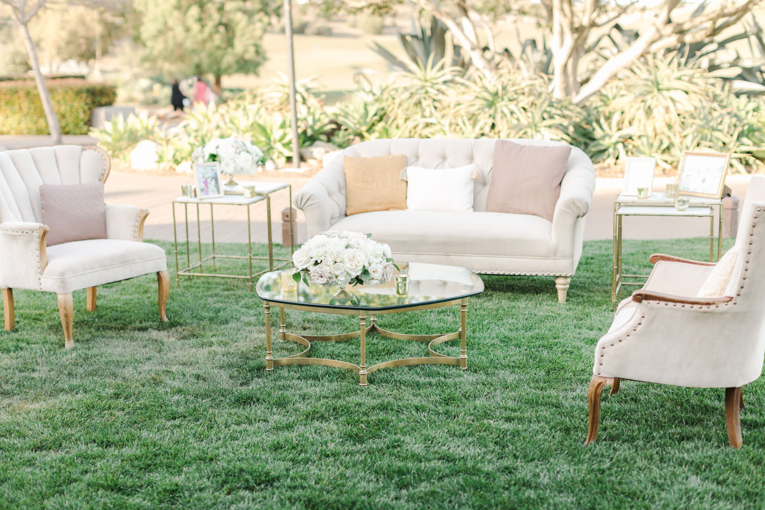 Wedding lounge with white sofa and armchairs with pillows and coffee tables, Cavin Elizabeth Photography