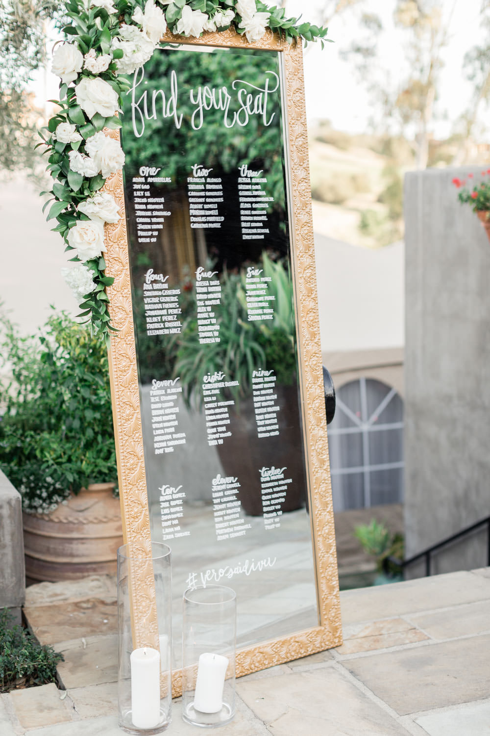 Wedding seating chart written on a mirror with white and green flowers, Cavin Elizabeth Photography