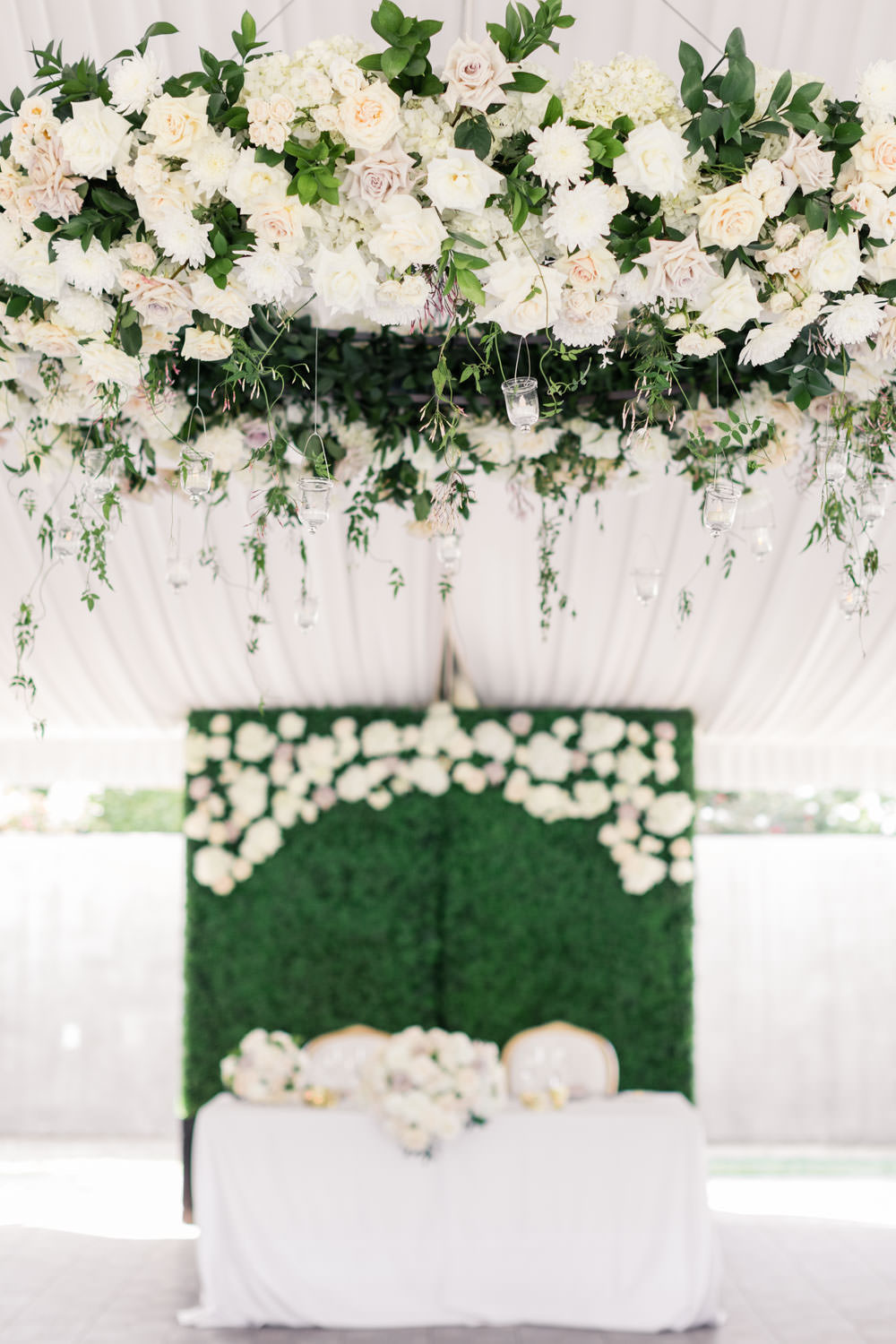 Floral chandelier with white roses and greenery and luxury sweetheart table with green hedge backdrop, Cavin Elizabeth Photography