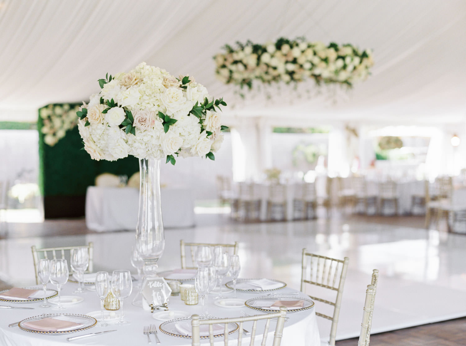 Film photo of a wedding reception tall centerpiece with white and green flowers at the Santaluz Club tented reception, Cavin Elizabeth Photography