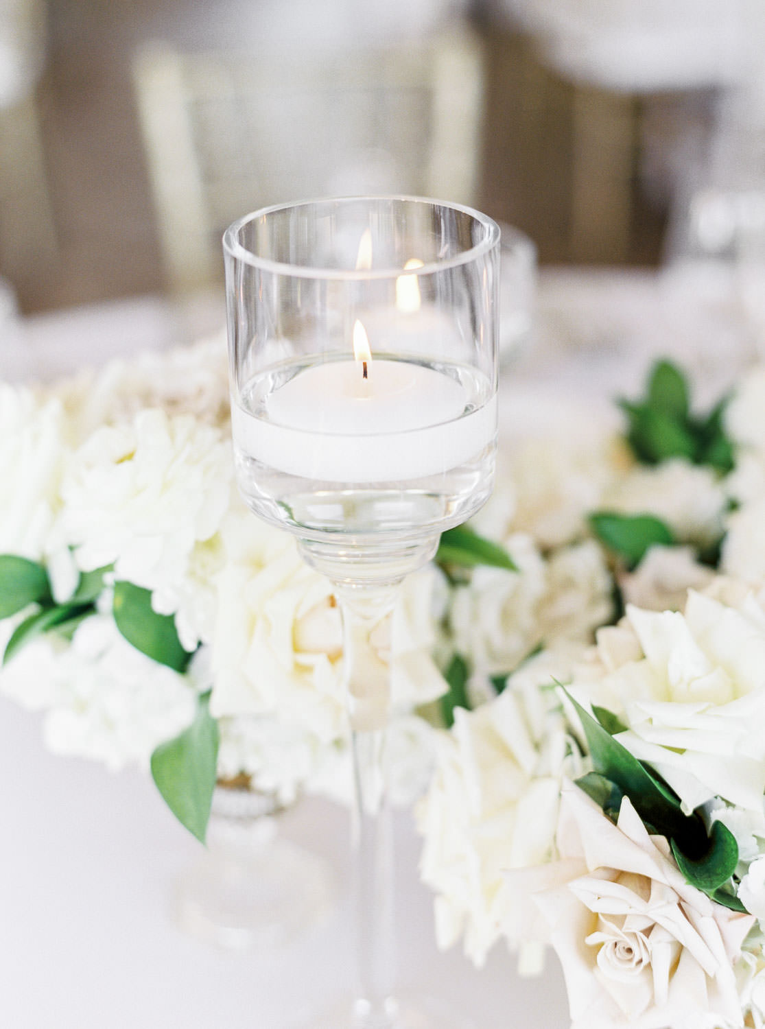 Film photo of a candle in a tall votive, wedding reception tall centerpiece with white and green flowers at the Santaluz Club tented reception, Cavin Elizabeth Photography