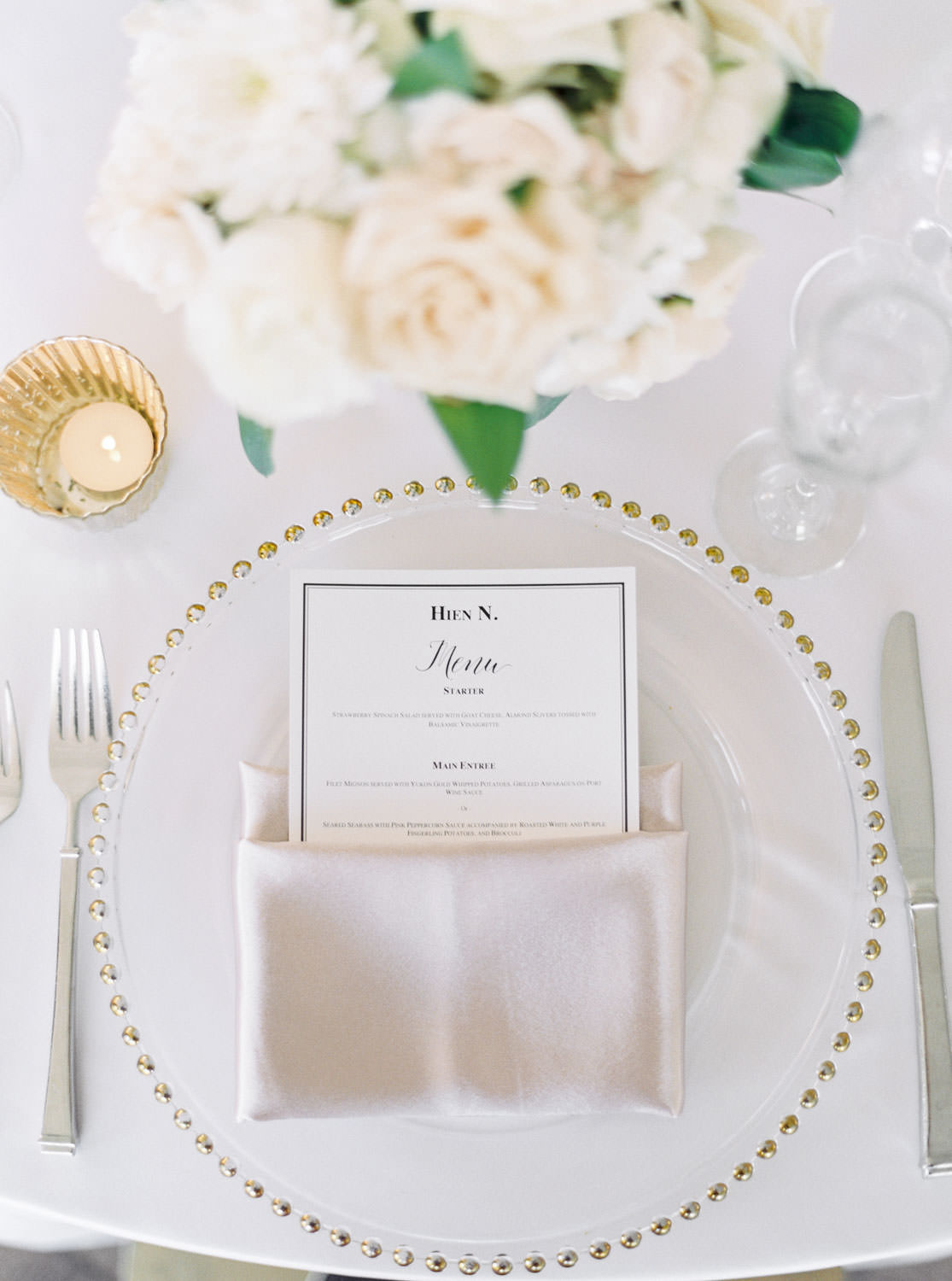 Gold beaded charger with white and black menu with lavender mauve napkin, wedding reception tall centerpiece with white and green flowers at the Santaluz Club tented reception, Cavin Elizabeth Photography