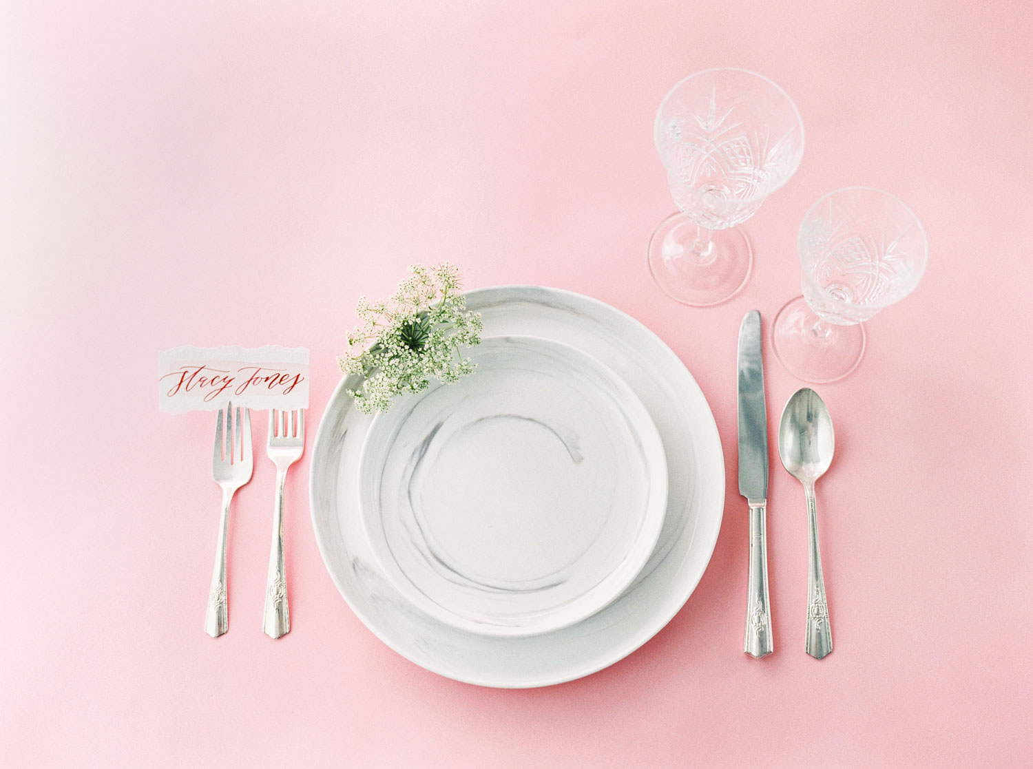 Wedding place setting with menu escort card on hand torn paper and clear glassware with marble plates, Pink backdrop wedding editorial on medium format Contax 645 Fuji 400h film by Cavin Elizabeth Photography