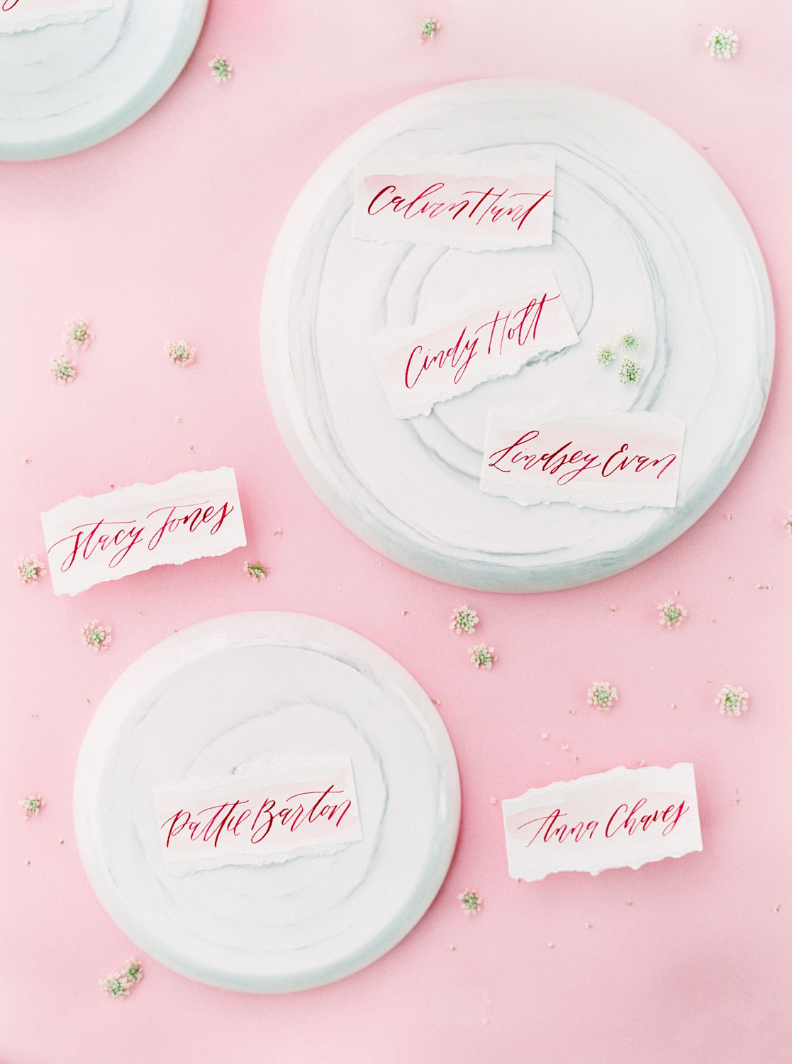 Escort cards deep pink calligraphy on hand torn paper on marble plates, Pink backdrop wedding editorial on medium format Contax 645 Fuji 400h film by Cavin Elizabeth Photography