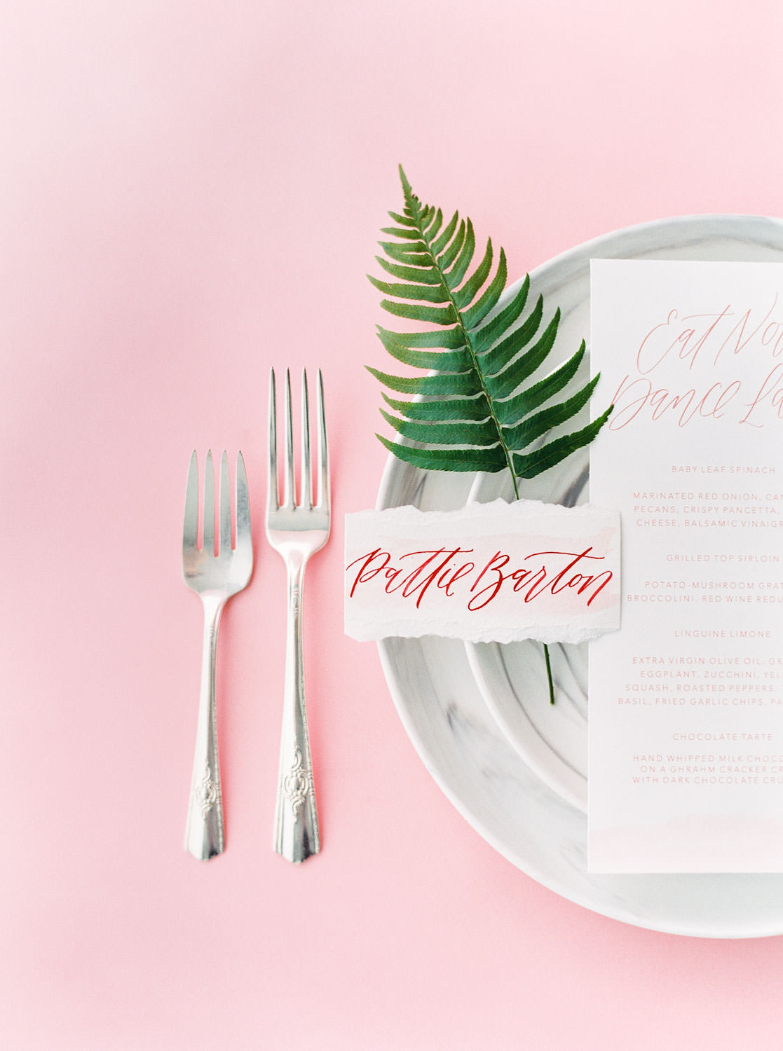 Wedding place setting with menu escort card on hand torn paper a fern and pink and clear glassware with marble plates, Pink backdrop wedding editorial on medium format Contax 645 Fuji 400h film by Cavin Elizabeth Photography