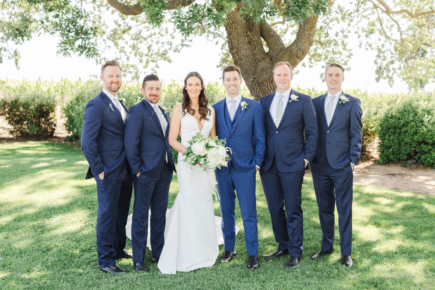 Bride and groom with groomsmen in navy suits for Gainey Vineyards wedding, Cavin Elizabeth Photography