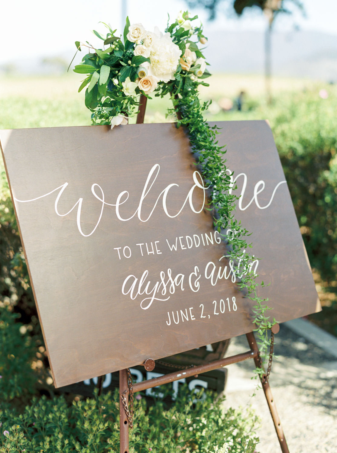 Wedding welcome sign with white calligraphy on wood captured on medium format film, Cavin Elizabeth Photography