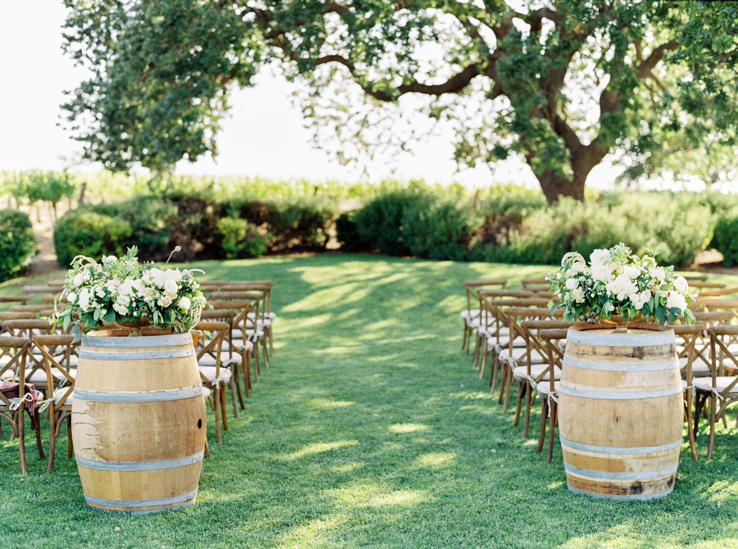 Wedding ceremony on lawn with large tree and arrangements on barrels with white and green bouquet with trailing ribbons captured on medium format film, Cavin Elizabeth Photography